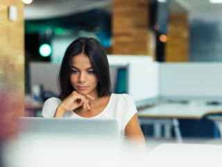 Woman in office looking at laptop