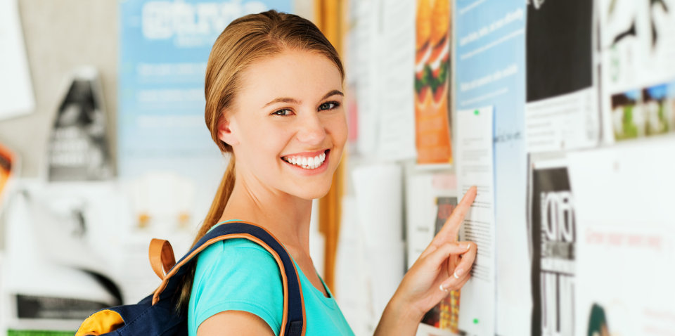 Girl looking at an ad on a bulletin board.