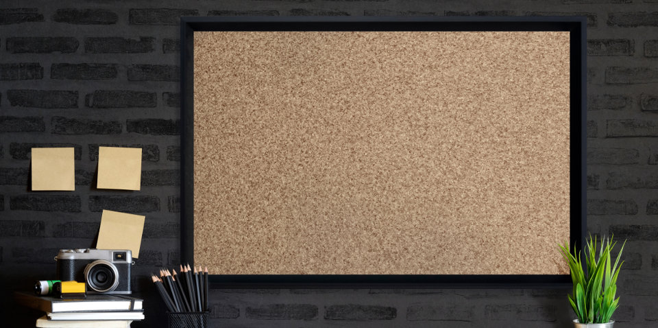 Cork board with black border in office.