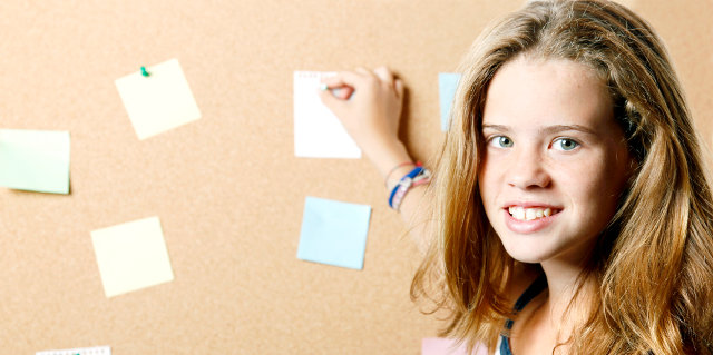 Young female student posting a note on a cork board.