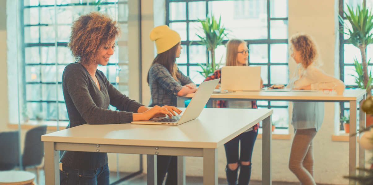 Four young women using standing desks at the office.