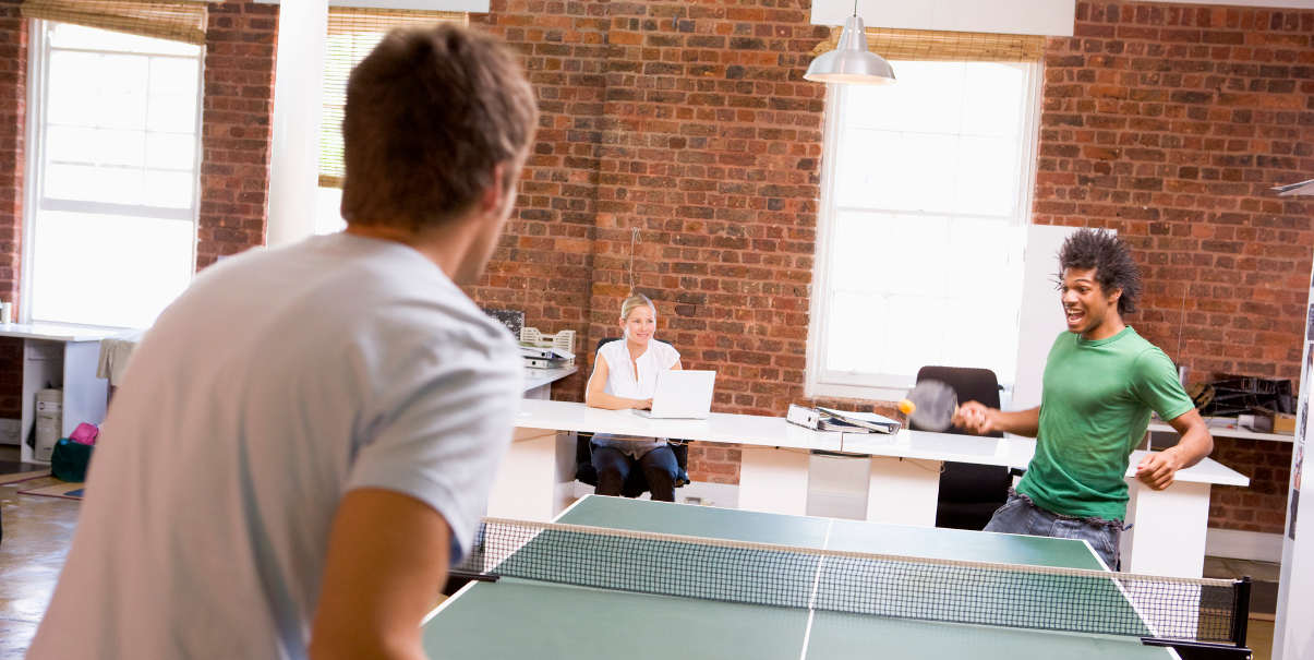 Coworkers playing table tennis