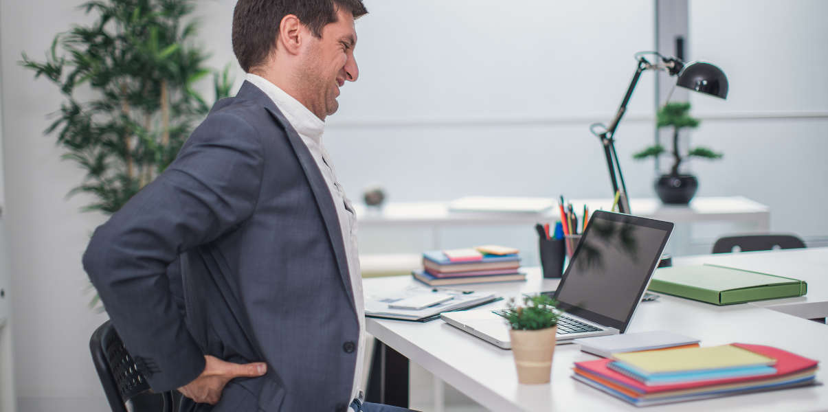 Businessman experiencing back pain.