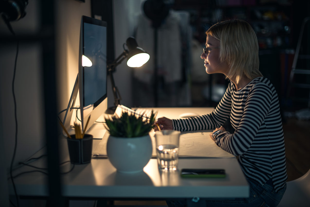 Woman working at her desk at night using a desk lamp.