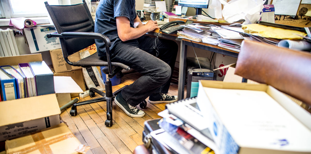 Man working in a messy, cluttered office.