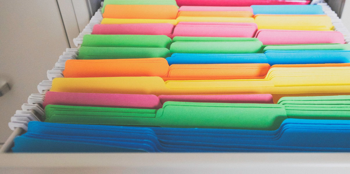 Close-up of colorful file folders in file cabinet drawer.
