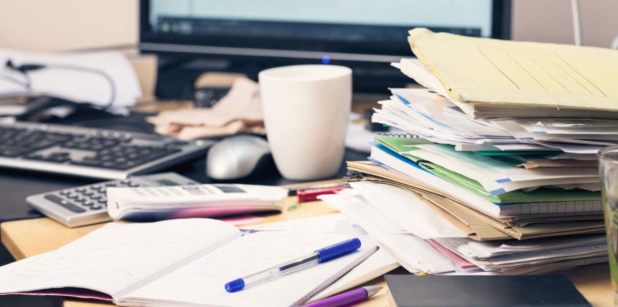 Close-up of messy desk covered in loose papers.