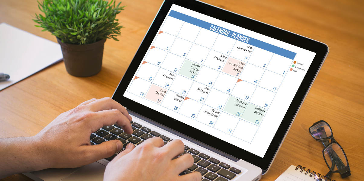 Hands typing on a laptop with a calendar planner on screen