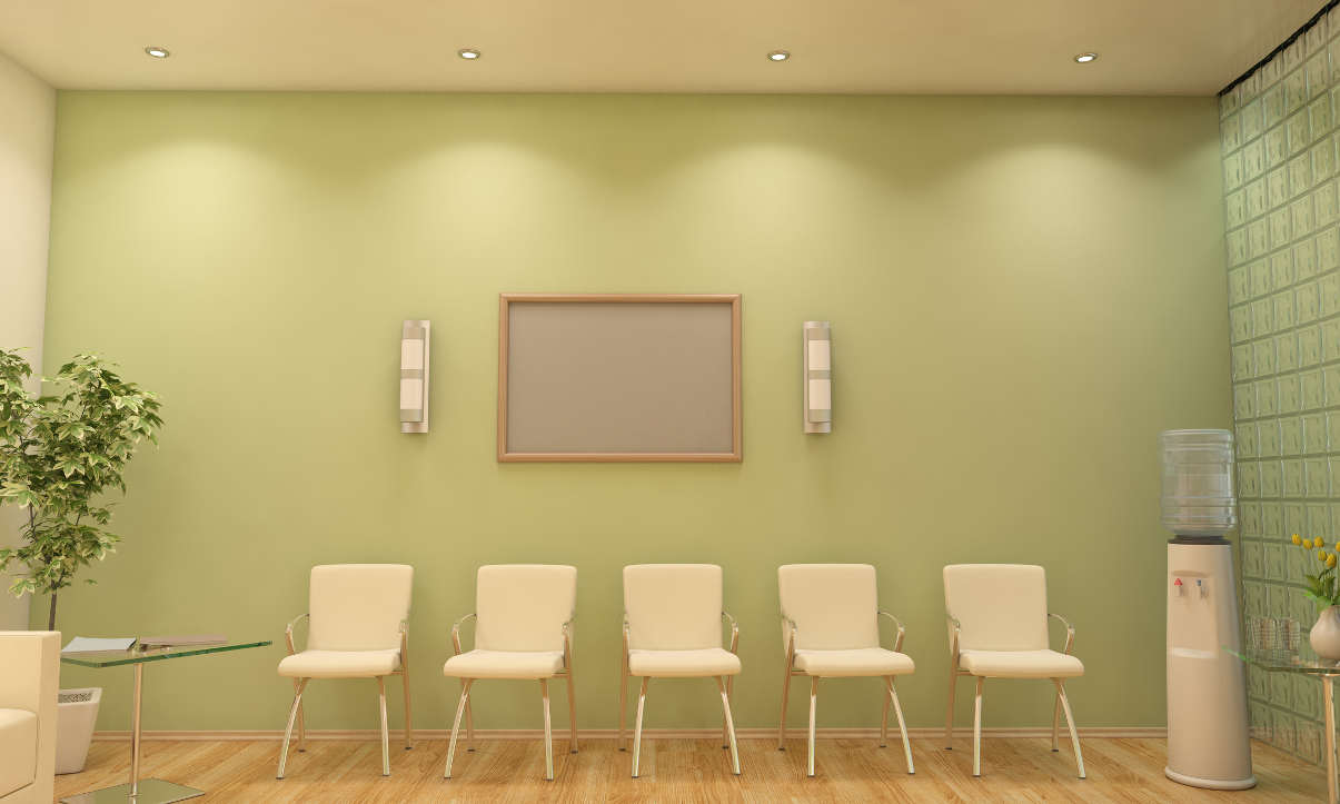 Minimalist waiting room with green walls and white chairs