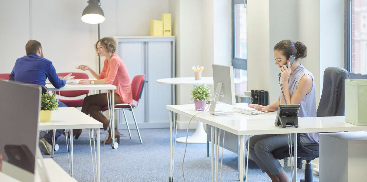 Woman using an L-shaped desk in a bright office environment