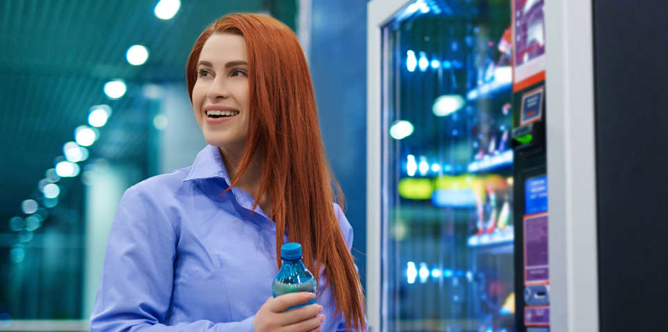 Smiling woman buying bottled water from vending machine.